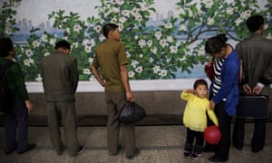A girl holds a red balloon as she and others wait for a train at a subway station visited by foreign reporters during a government organised tour in Pyongyang.