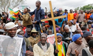 A protester in Harare carrying a cross