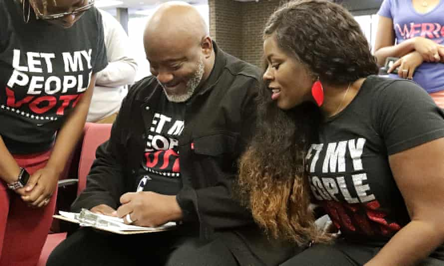 In this photo, former felon Desmond Meade and president of the Florida Rights Restoration Coalition, left, fills out a voter registration