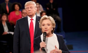 Donald Trump lurks behind Hillary Clinton as she answers a question from the audience.