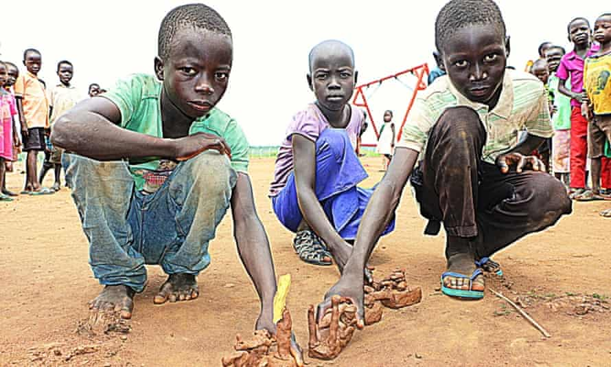 Children show their toys made out of red earthen mud.