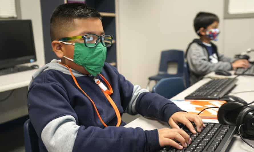 kids use computers while wearing masks