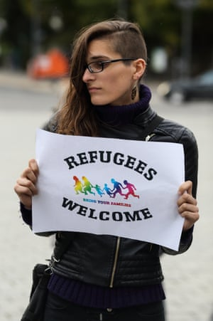 A woman in Berlin holds a sign welcoming refugees.