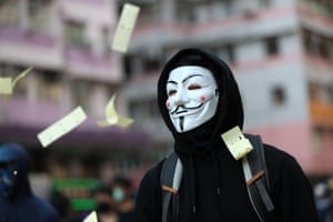 """Ceremonial """"joss paper"""" used in memory of those who died for democracy flutters around a protester wearing a V for Vendetta mask during a demonstration in the Sham Shui Po district."""