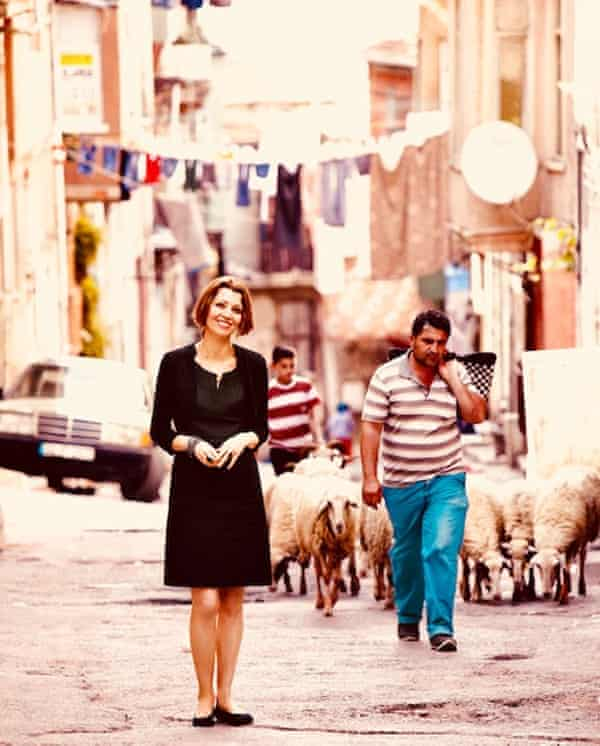 Elif Shafak in a street in Istanbul with a flock of sheep behind her and washing hung over the street