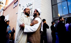 Two Muslim men greet each other outside a mosque in Tower Hamlets.