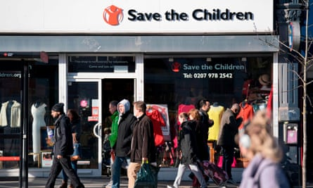 People walk past a high street branch of a Save the Children charity shop in south London.
