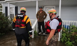 North Carolina officials help a resident walk through flooded waters in Lumberton. More than a third of people in Lumberton live below the poverty line.