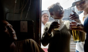 Men and women drink in a shebeen, an illegal tavern usually in someone's home, in Gugulethu, about 15km from the centre of Cape Town.