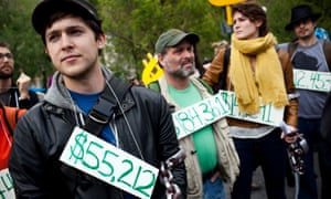 Occupy Wall Street demonstrators wear signs representing their student debt during a protest in New York.