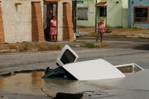Ciudad Juarez, MexicoWomen react near a pick-up truck submerged in a sinkhole at a street damaged by heavy rains