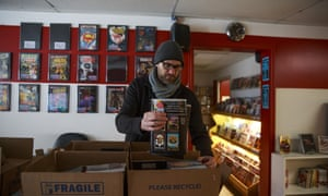 Matt Traughber, an owner of the Vintage Phoenix comic bookstop in Indiana, packs comics to distribute to subscribers a day early, on 24 March.