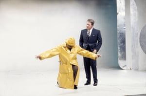 Eric Morecambe kneels in a yellow raincoat as Ernie Wise looks on