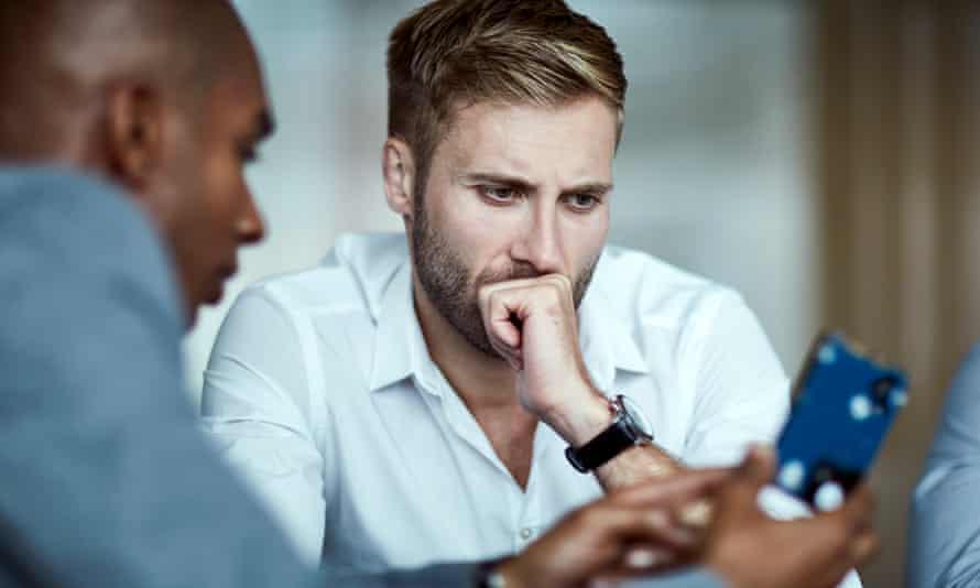 Serious businessmen examining electronic device