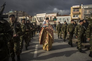 An Orthodox priest holds a cross as he is accompanied by a guard of honour during an Epiphany ceremony to bless the water in Mytilene port, on the Greek island of Lesbos