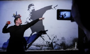 A man poses for a picture with a Banksy art work at the exhibition in Moscow