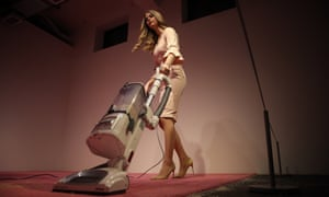 An Ivanka Trump look-alike vacuums up crumbs thrown by visitors as part of Jennifer Rubell's installation.