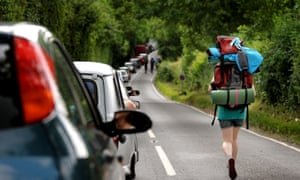 A woman walks along the B3136 past queuing traffic as festival-goers make their way to Glastonbury festival.