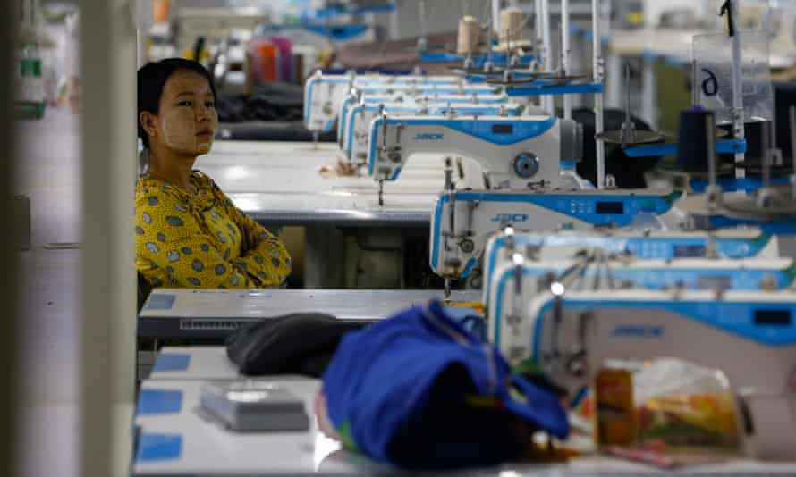 A woman sits near sewing machines as workers occupy a recently closed garment factory in Myanmar to demand their salaries.