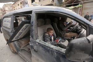 A man and a child sit in a damaged car after airstrikes by the Assad regime and Russia hit a marketplace in the Eriha district of Idlib, Syria