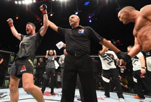 The referee raises the arm of Michael Bisping to signal that he's retained his UFC middleweight title.