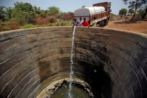 A dried-up well is refilled with water from a water tanker in Thane district in the western state of Maharashtra