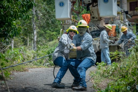 Jose Luis Gonzalez and Jose Ralat from the Puerto Rico Electric Power Authority pull a fallen line while restoring power to a single family home.