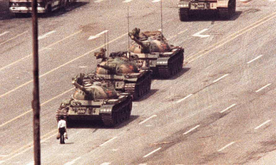 A man stands in front of a convoy of tanks in the Avenue of Eternal Peace in Beijing, 5 June 1989