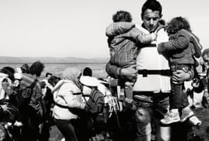 A father carries his two children from the boat after landing.