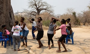 The women take a break from their mine-clearing work, dancing to music on the radio