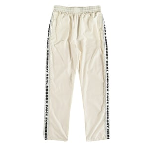 white tracksuit bottomes with black writing down the side of the legs Woodwood