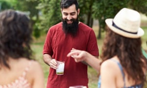 Portrait Of Smiling Bearded Man With Drink Talking To His Unfocused FriendsPortrait of cheerful man with beard and drink in glass smiling while looking down and talking to unrecognizable friends in garden.Bokeh