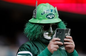 A suitably attired Jets fan checks his phone.
