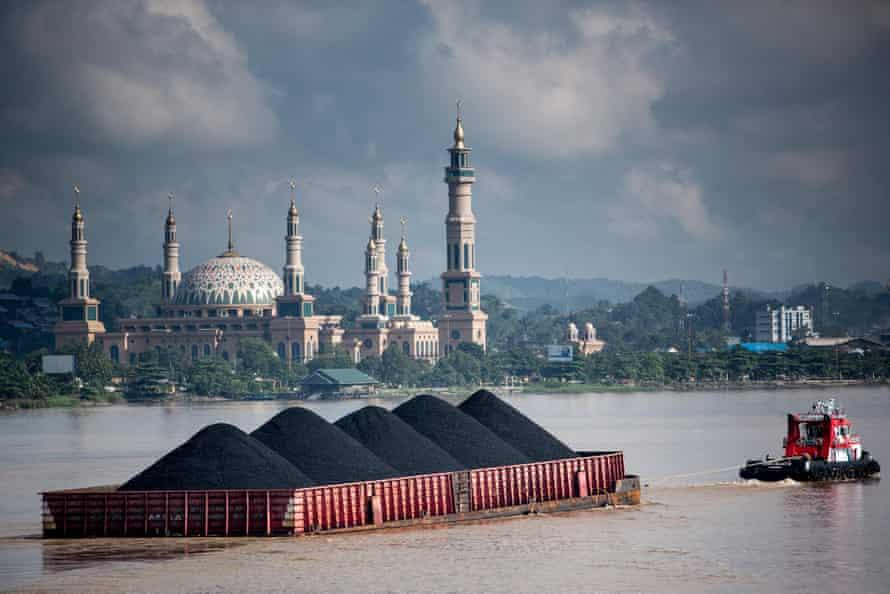 Coal barges come down the Mahakam river in Samarinda, East Kalimantan, Indonesian Borneo.