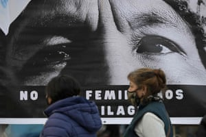 Two women in masks walk past a portrait of Milagro Sala, the leader of Tupac Amaru movement for justice.