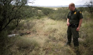 A border patrol agent looks at the body of a Guatemalan migrant Misael Paiz, 25, who died in the Sonoran desert after traveling over 2,000 miles to cross the US-Mexico border in Pima County, Arizona, in September.