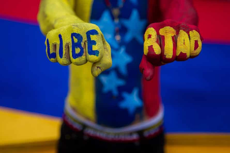 An anti-government protester with the word 'freedom' painted on his fists in the colours of the Venezuela flag.