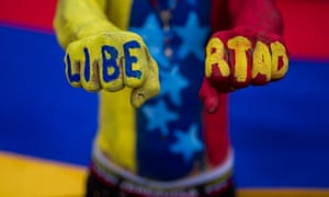 A Venezuelan opposition demonstrator poses with the word 'freedom' painted on his fists during a demonstration against the government.