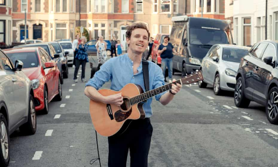 Al Lewis plays the guitar and leads a singalong in Northumberland Street, Cardiff, while other residents dance in the street behind him