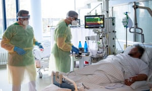 Senior doctor Thomas Marx (L) talks to a patient infected with the novel coronavirus Covid-19 in an intensive care unit at the hospital in Freising.