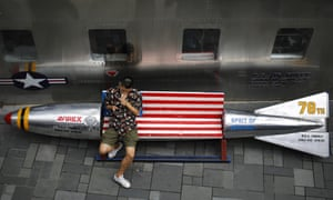 A man lights a cigarette on a bench in a shape of a mock aerial bomb outside a fashion boutique selling U.S. brand clothing at a mall in Beijing.