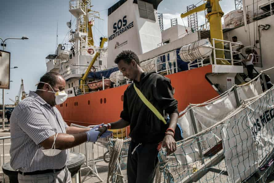 Authorities check the migrants as they disembark from the Aquarius