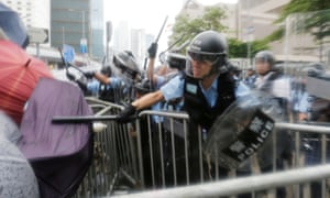 Riot police use their batons to bludgeon protesters trying to defend themselves from pepper spray with umbrellas