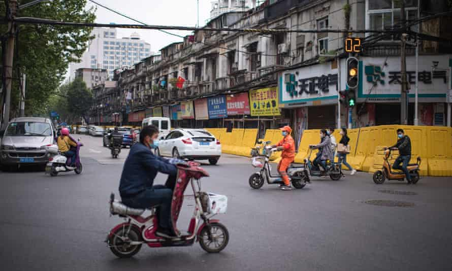 Street scene in Wuhan, China with people in masks on scooters, and cars