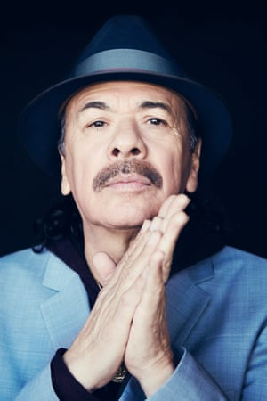Carlos Santana in a trilby and with his hands together in front of him