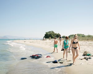 Tourists walk along a beach in Kos, past lifejackets abandoned by arriving refugees.