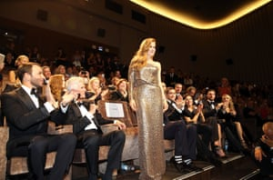 A woman in a gold evening gown stands in a seated crowd in a cinema