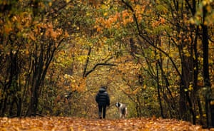 A woman walks her dog in a park in Sofia, Bulgaria