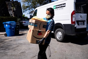 An Amazon delivery woman delivers packages amid the coronavirus pandemic in Los Angeles, California, USA, 26 March 2020.