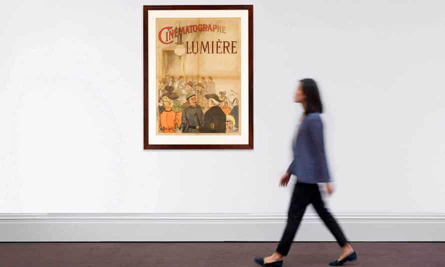 Woman walks past poster for Lumière brothers short film in gallery